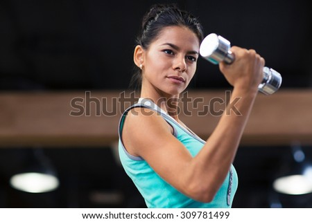 Portrait of a charming woman workout with dumbbells in fitness gym - stock photo