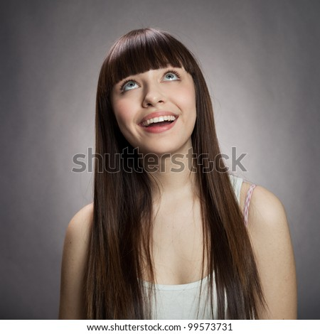 Portrait of a charming young female smiling against dark background - stock photo