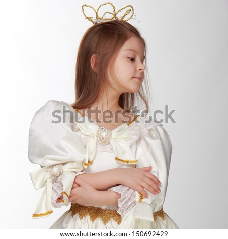 Portrait of a charming young girl in a beautiful fancy dress on white background on Holiday