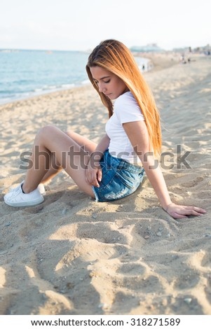 Portrait of a charming young hipster girl enjoying good day and rest after walking along coastline, stylish woman dreams while sitting alone near the sea, attractive stylish female posing on the beach - stock photo