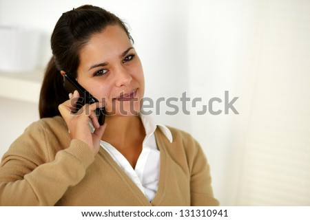 Portrait of a charming young woman conversing on mobile phone while is looking at you