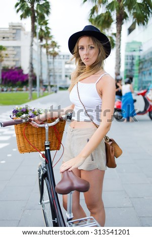 Portrait of a charming young woman dressed in trendy clothing rest after riding around the city on her vintage bike, wonderful female enjoying leisure time while strolling with retro bicycle outdoors - stock photo