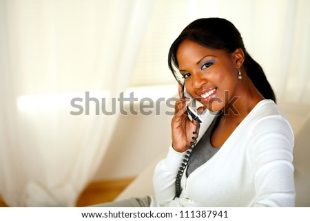 Portrait of a charming young woman looking at you while conversing on phone. With copyspace - stock photo