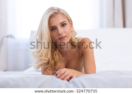 Portrait of a charming young woman lying on the bed and looking at camera - stock photo
