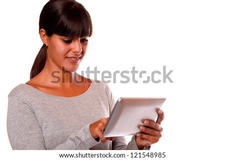Portrait of a charming young woman using her tablet pc on grey dress standing over white background