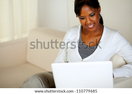 Portrait of a charming young woman working on laptop while sitting on sofa