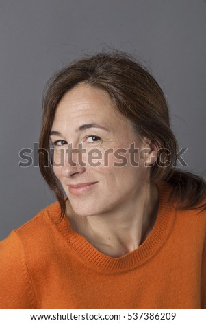 portrait of a cheeky beautiful middle aged woman with sexy natural wrinkles for modern beauty and playful wellbeing, grey background studio