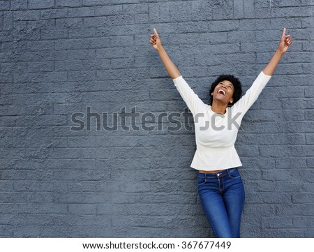 Portrait of a cheerful african woman with hands raised pointing up - stock photo