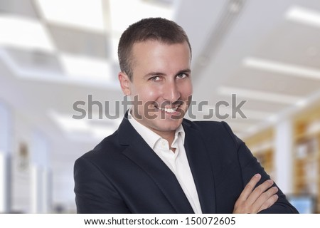 Portrait of a cheerful, attractive business man in a modern office environment. - stock photo