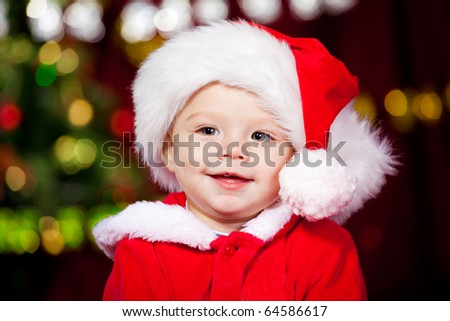 Portrait of a cheerful baby boy in Santa hat - stock photo