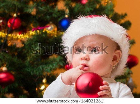 Portrait of a cheerful baby girl with red bauble and Santa hat - stock photo