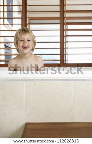 Portrait of a cheerful boy in bathtub