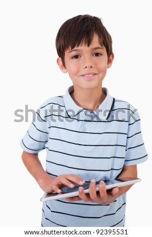 Portrait of a cheerful boy using a tablet computer against a white background - stock photo