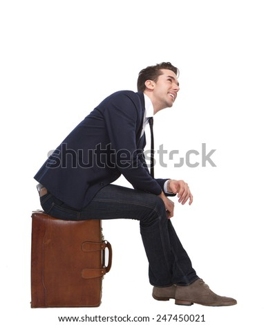 Portrait of a cheerful business man sitting on suitcase on isolated white background - stock photo