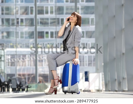 Portrait of a cheerful business woman talking on mobile phone and sitting on suitcase at airport - stock photo