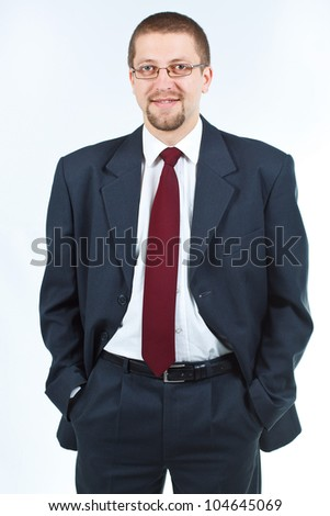 Portrait of a cheerful businessman in suit and tie, with glasses, hands in pockets, smiling confidently into camera - isolated on white - stock photo