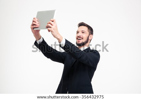 Portrait of a cheerful businessman making selfie photo on tablet computer isolated on a white background - stock photo