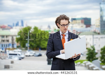 Portrait of a cheerful businessman with laptop, summer street outdoors - stock photo
