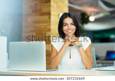 Portrait of a cheerful businesswoman sitting at the table in office and looking at camera - stock photo
