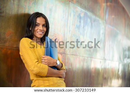 Portrait of a cheerful businesswoman standing with folder in hallway and looking at camera - stock photo
