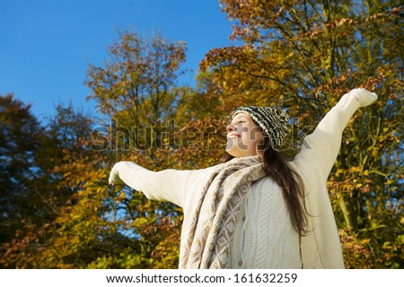 Portrait of a cheerful, carefree woman enjoying sunny autumn day with arms outstretched - stock photo