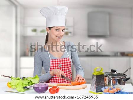 Portrait of a cheerful cooking woman in the kitchen - stock photo