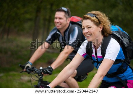 Portrait of a cheerful couple enjoying a bike ride in nature - stock photo
