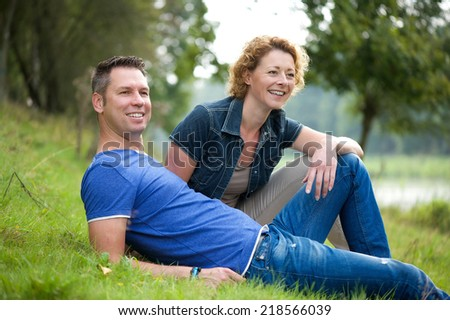 Portrait of a cheerful couple sitting on grass outdoors - stock photo