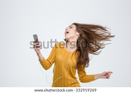 Portrait of a cheerful cute woman listening music in headphones and dancing isolated on a white background - stock photo