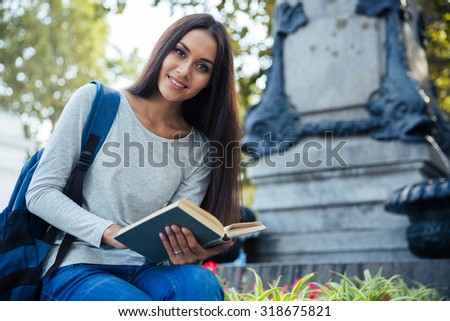 Portrait of a cheerful female student holding book and looking at camera outdoors
