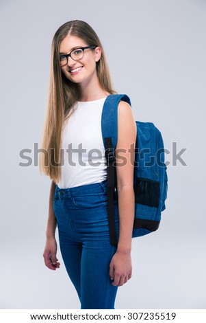 Portrait of a cheerful female teenager with backpack standing isolated on a white background. Looking at camera - stock photo