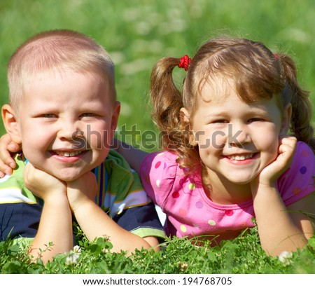 Portrait of a cheerful girl and boy lying fun in outdoor