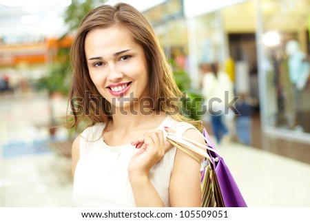 Portrait of a cheerful girl holding a bunch of shopping bags