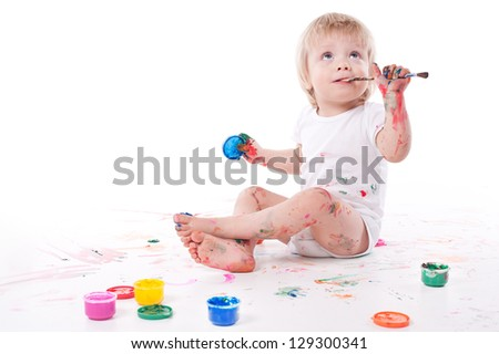 portrait of a cheerful grimy kid. playing with paint. on a white studio background.