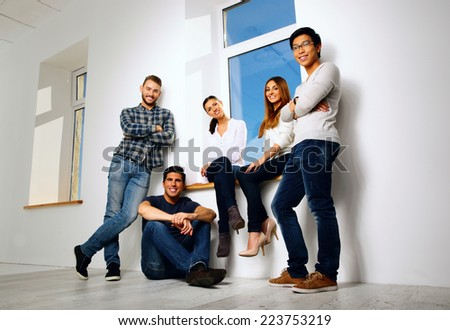 Portrait of a cheerful group friends looking at the camera - stock photo