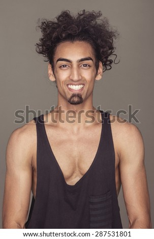 Portrait of a Cheerful Handsome Athletic Young Man with Curly Hair in Casual Sleeveless Shirt, Smiling at the Camera Against Gray Background. - stock photo