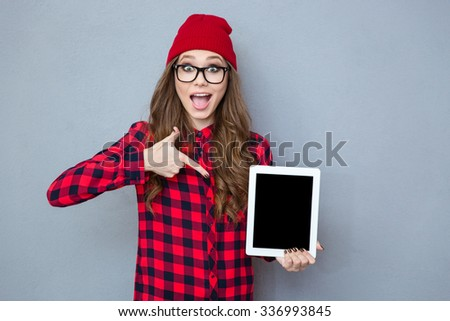 Portrait of a cheerful hipster woman pointing finger on tablet computer screen over gray background - stock photo