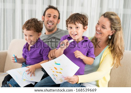 Portrait of a cheerful kid drawing something with mum sitting on the foreground  - stock photo