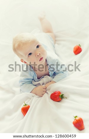 portrait of a cheerful kid with strawberries - stock photo