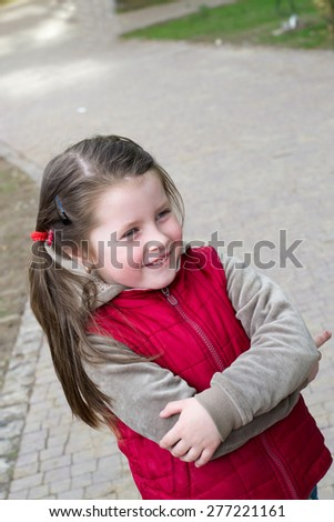 Portrait of a cheerful little baby girl in a jacket in the park in spring - stock photo
