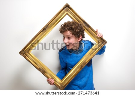 Portrait of a cheerful little boy holding picture frame - stock photo
