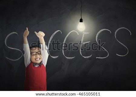 Portrait of a cheerful little boy showing thumbs up with bright lightbulb and Success word on the chalkboard, shot in the class