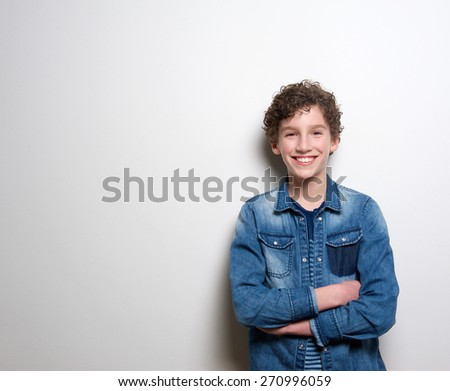 Portrait of a cheerful little boy smiling with arms crossed on white background - stock photo