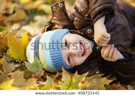 Portrait of a cheerful little boy wallow in fall foliage. Smiling funny little boy covered with autumn leaves. Little boy lying and having fun among multicolored autumn leaves in the park - stock photo