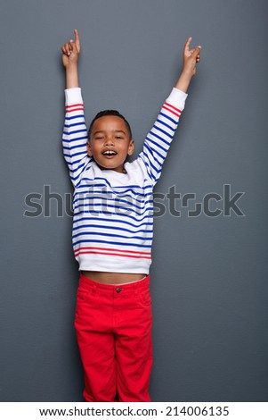 Portrait of a cheerful little boy with arms raised and pointing up on gray background - stock photo