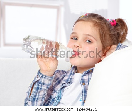 portrait of a cheerful little girl drinking water from a bottle on the abstract background - stock photo