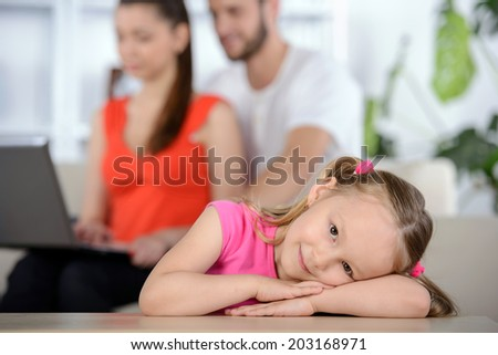 Portrait of a cheerful little girl on a background of parents using laptop