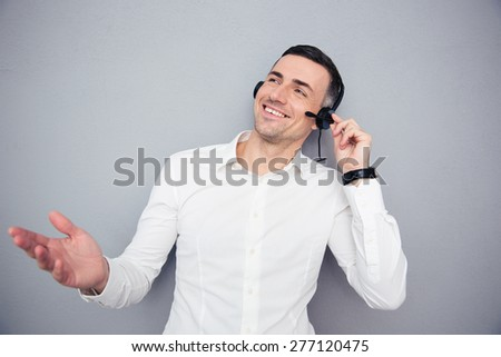 Portrait of a cheerful male operator looking away over gray background - stock photo