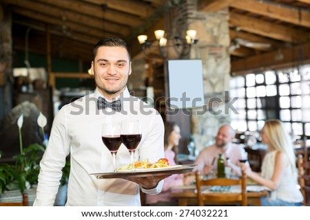 Portrait of a cheerful male waiter with a tray in his hand at the restaurant - stock photo