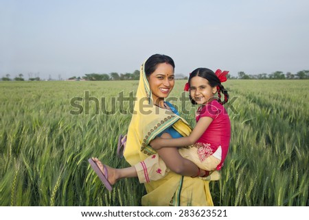 Portrait of a cheerful mother and daughter in the field - stock photo